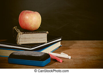 Apple, Books and Chalks with Blackboard Background