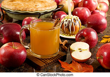 A cup of hot apple cider, caramel apple and apple pie surrounded by fresh fruits