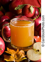 A cup of hot apple cider surrounded by fresh fruits