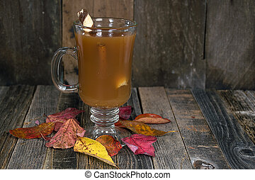 apple cider on wood with fall leaves