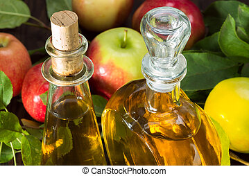 apple cider vinegar in a glass vessel and apples - apple...