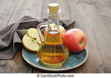 Apple cider vinegar in glass bottle and fresh apples on...