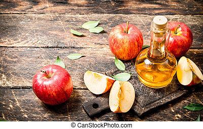 Apple cider vinegar, red apples . On wooden background.