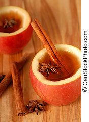 Spiced apple cider in hollowed out apples with cinammon and star anise