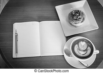 Apple cinnamon roll served with latte art coffee and notebook on the table at restaurant black and white tone