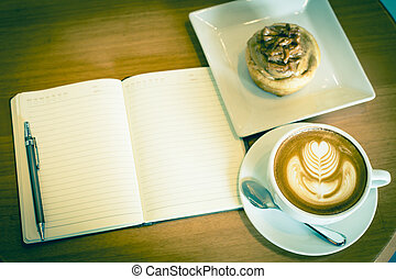 Apple cinnamon roll served with latte art coffee and notebook on the table at restaurant