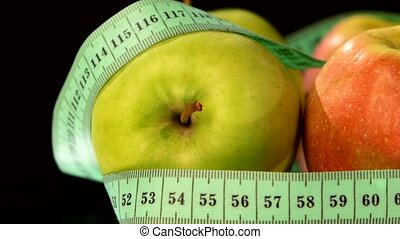 Apple collection with measuring tape, rotation, reflection, on black, close up