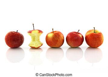 Apple core among whole apples, reflecting on white background.
