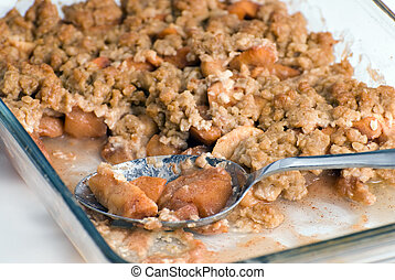 Closeup view of a spoon sitting in a glass dish containing apple crisp