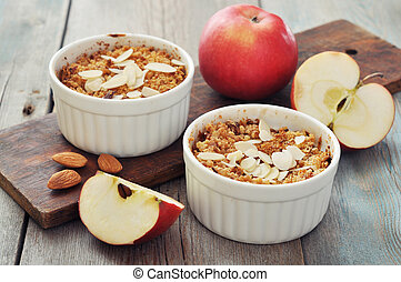 Apple crumble in ceramic molds with fresh apples on wooden background
