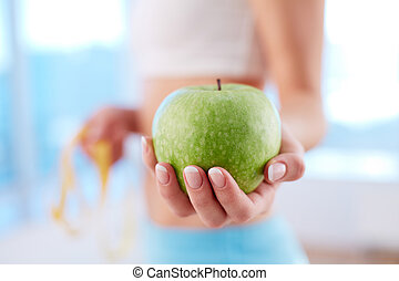Apple diet - Close-up of a fit woman holding a fresh apple
