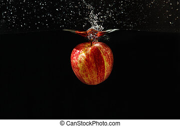 Apple falling into the water with a splash on a dark background closeup