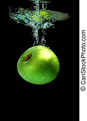 Green apple falling into water