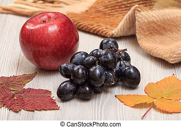 Apple, grapes, checkered plaid and dry leaves on wooden boards. An autumn still llife.