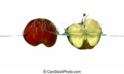 Apple halves plunging into water