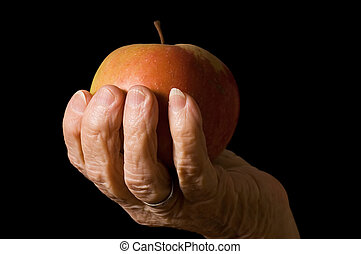 Apple in a hand of old woman