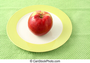 Apple in plate on a green cloth background