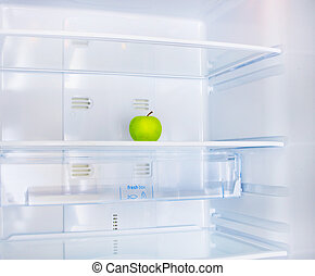 apple in the fridge - green apple in the empty white fridge
