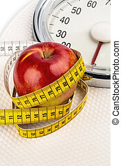 apple is on a scale - on a bathroom scale is an apple. ...