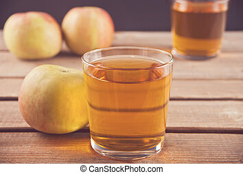 Apple juice and apples on wooden table. Selective focus