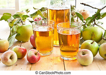Clear apple juice and a variety of fresh organic apples