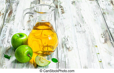 Apple juice in a glass jar with apples.