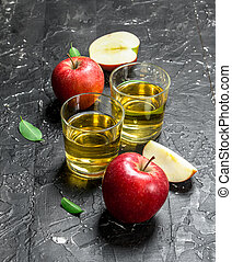 Apple juice in a glass jar with fresh apples in a box.