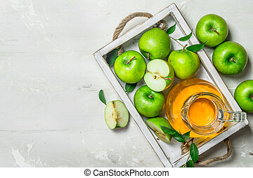 Apple juice in a glass jar with fresh apples.