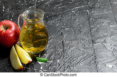 Apple juice in a glass jar with red fresh apples.