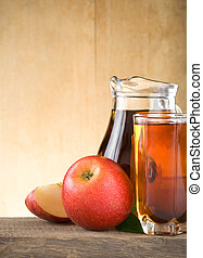 apple juice in glass and slices on wood