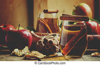 Apple juice with cinnamon in a glass and fresh apples on a vintage wooden background, selective focus and shallow depth of field and toned image