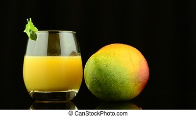 Apple mango and juice rotating on black background.