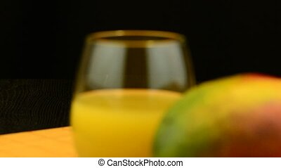 Apple mango and juice sliding on wood table top on black...