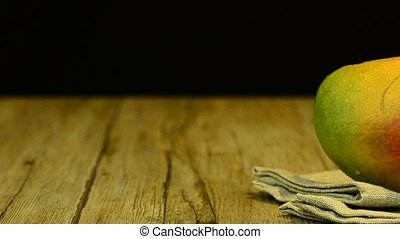 Apple mango and juice sliding on wood table top on black background.