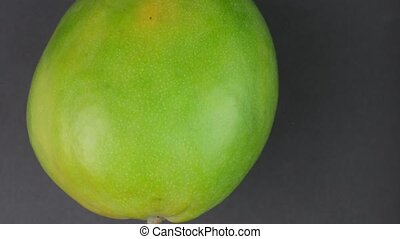 Apple mango rotating on black background. 4 K resolution