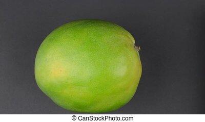 Apple mango rotating on black background. 4 K resolution.