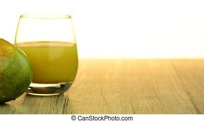 Apple mango and juice sliding on wood table top on white...