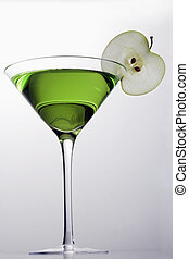 Apple Martini mixed drink with apple slice garnish on grey background