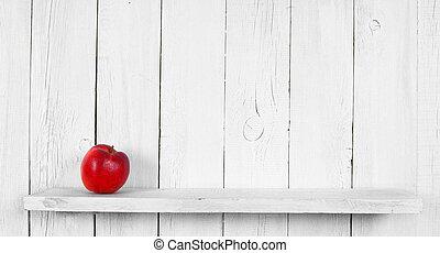 Apple on a wooden shelf.