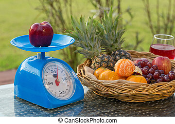 apple on kitchen scale with fruits in basket an wine glass -...