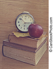 Apple on old books with brown clock