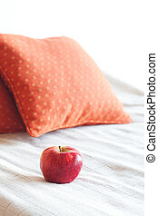 apple on the bed with two pillows
