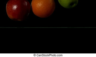 Apple orange and lime plunging into water on black...