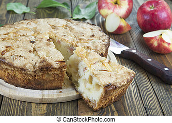 Apple pie. charlotte - Apple pie and red apples on a wooden...