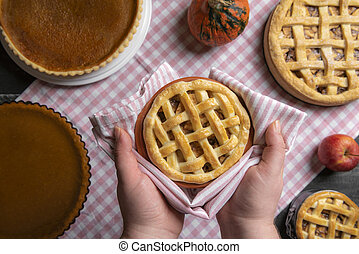 Apple pie held in hands over a table with many pies. Sweet pies baking. Above view.
