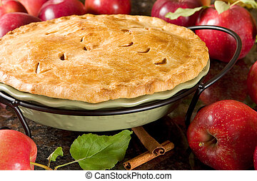 Homemade apple pie surrounded by fresh apples
