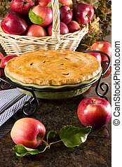 Homemade apple pie surrounded by fresh fruits