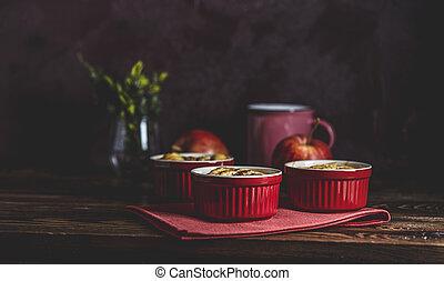 Apple pie in ceramic baking molds ramekin on dark wooden table. Close up, shallow depth of the field.
