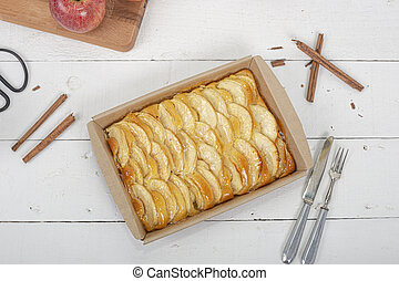 Apple pie, ingredients - apples and cinnamon on white rustic wooden background - top view