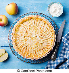 Apple pie on a blue wooden background. Top view